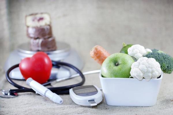 Friss gyümölcsök, zöldségek, inzulinpumpa, vércukorszintmérő készülék, fonendoszkóp, műanyag piros szív és a háttérben konyhai mérlegen krémes péksütemények egymáson.
