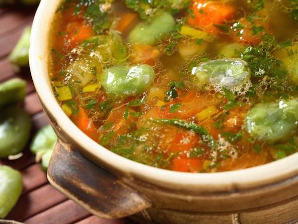 Lábosban lévő forró zöldségleves, a tetején összevagdalt turbolyával.