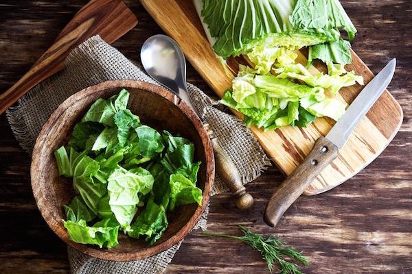 Kínai kel felaprítva fa salátástálban, mellette a zöldség, kés, vágódeszka.