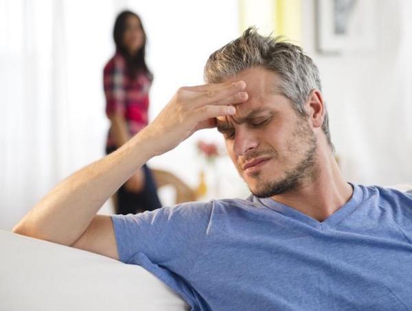 Fejét fájlaló férfi a kanapén, háttérben a felesége.