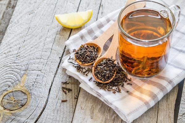 Fekete tea üvegpohárban, mellette citromgerezd és a szárított tealevelek kis mérőkanálban.