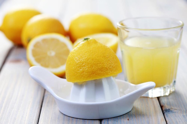 Félbevágott citromok, kerámiafacsaró és egy pohár citromlé.