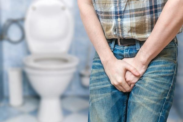 Egy férfi topog a fürdőben, két kezét a nadrágjára szorítva.