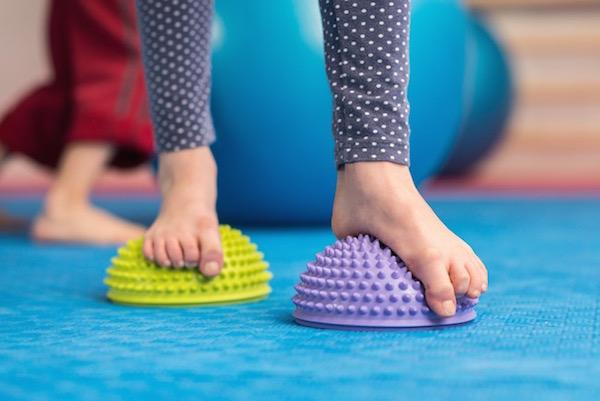 Kisgyerekek speciális lúdtalptornája gumis féllabdán.