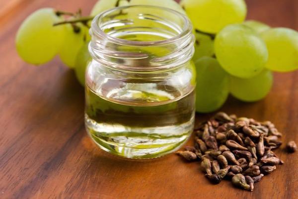 Fehér szőlő, szőlőmagok és kis üvegben zöldes színű szőlőmagolaj.