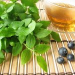 Fekete áfonya és levelei, mellettük a belőlük készült tea.