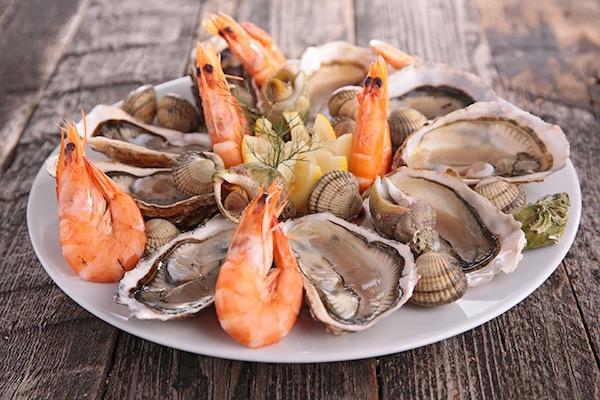 Tenger gyümölcsei, rákok, kagylók egy nagy fehér tányéron.