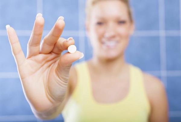 B10-vitamint mutat fel ujjai között egy sárga trikós nő.