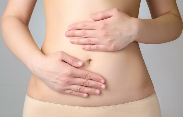 Testszínű fehérneműt viselő nő a köldöke köré helyezi mindkét kezét.