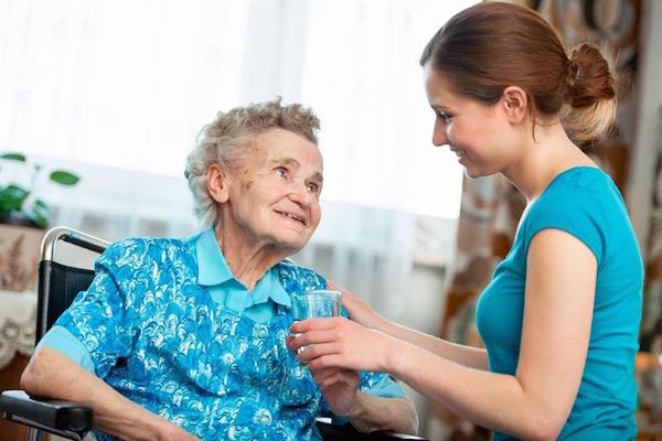 Idős néninek egy pohár vizet ad otthonában felnőtt unokája.