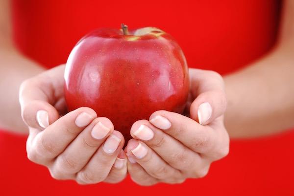 Egy szép piros almát tart kezei között egy piros ruhás lány.