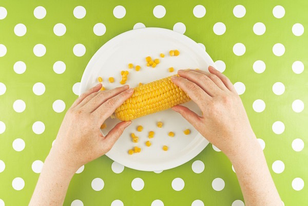 Főtt kukorica a tányéron, pöttyös asztalterítőn.