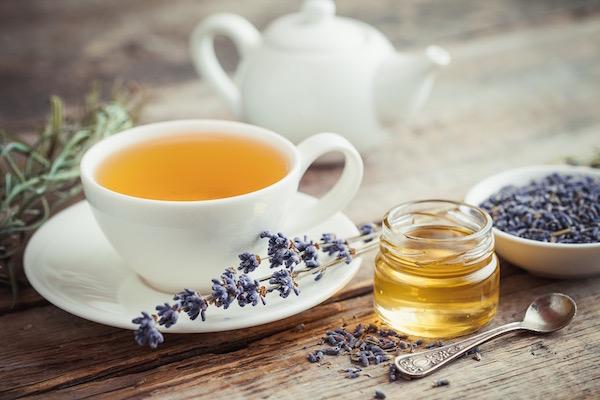 Levendulatea egy fehér csészében, mellette szárított levendulavirág, egy kis üvegcsében méz, a háttérben egy fehér teáskanna.