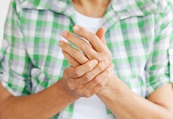 Kockás inges férfi a kézfejét fájlalja.