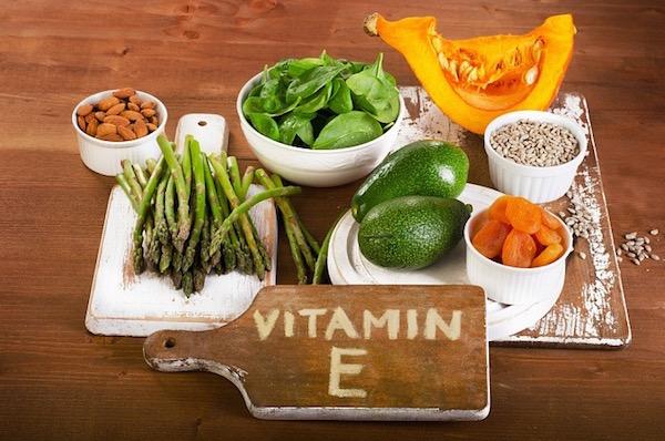 E-vitamin-tartalmú élelmiszerek egy tálcán: spárga, avokádó, aszalt sárgabarack, spenót, mandula, sütőtök.