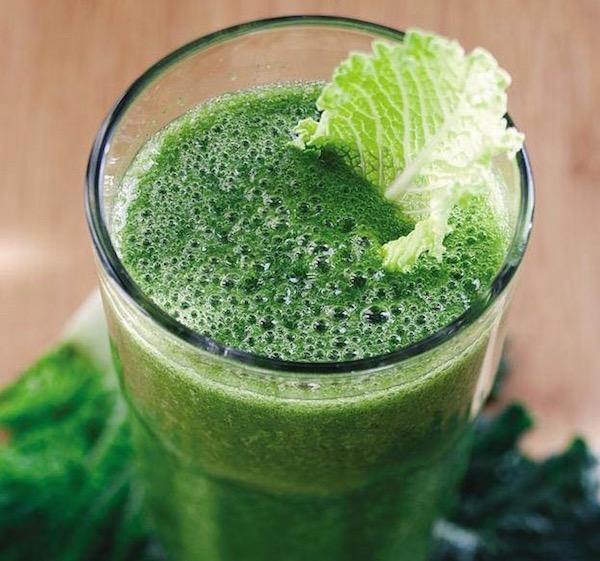 U-vitamint tartalmazó káposztalé üvegpohárban, benne egy kis kelkáposztalevél.
