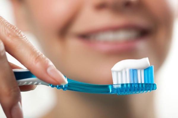 Fogkefén fehér színű fogkrém, a háttérben egy hölgy arca elmosódva.