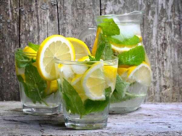 Citromfűszörp kancsóban és poharakban sok-sok citrommal, jéggel és citromfűlevelekkel.