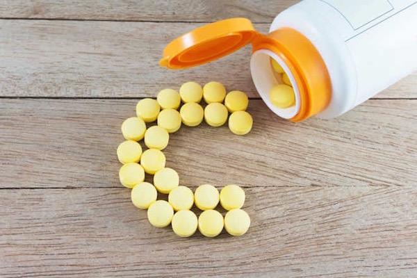 Dobozából kiszórt sárga színű C-vitaminok C betűt formázva.