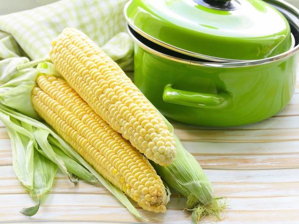Zöld lábas, mellette főznivaló csemege kukoricák.