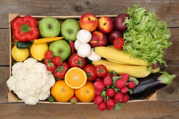 Egy felülről fotózott láda, amely teli van friss zöldséggel és gyümölccsel.