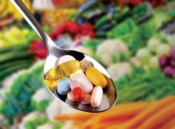 Rengeteg zöldség felett kanálban különféle méretű és színű vitaminok.