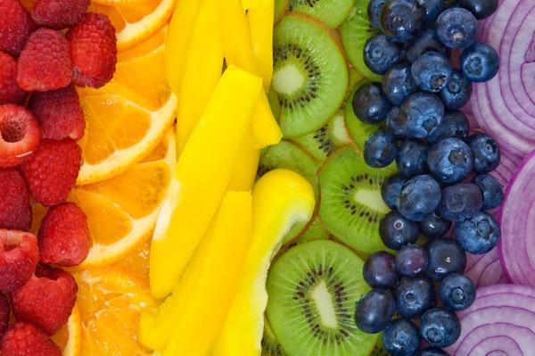 Különféle színű gyümölcsök és zöldségek egymás mellé szín szerint rakva: málna, narancs, citrom, kivi, áfonya és lila hagyma.
