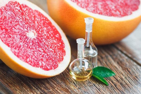 Félbevágott grépfrút, mellettük kis üvegcsében a gyümölcs illóolaja.