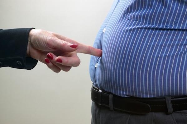 Kövér férfi felpuffadt hasát nyomja egy ujjával egy női kéz.