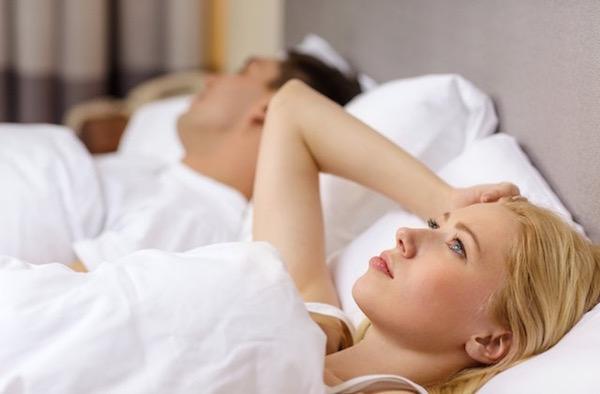 Álmatlanul, ébren fekszik párja mellett az ágyban egy fiatal nő.