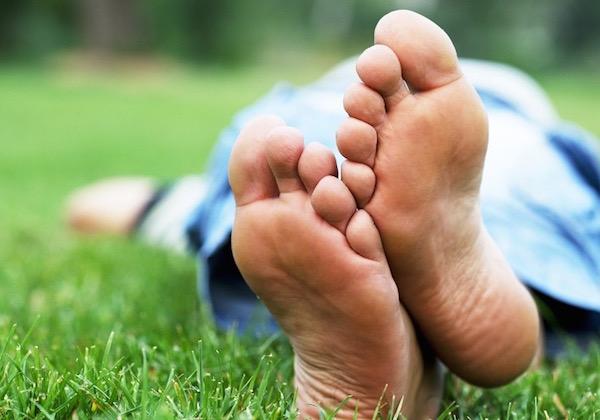 Mezítláb fekszik egy férfi a fűben, a fotó a talpáról készült.