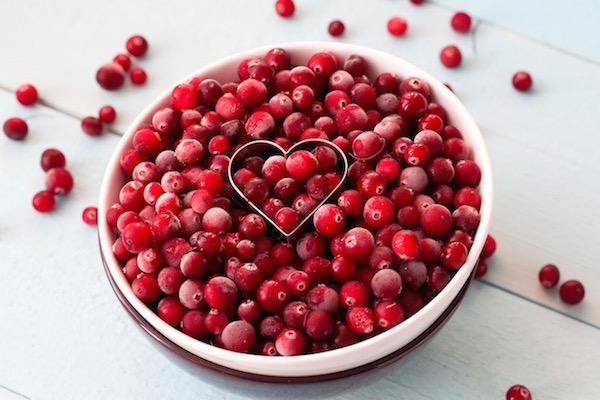 Medveszőlő piros bogyótermése egy nagy, lapos, fehér tálban, középen egy szív alakú kiszúróforma.