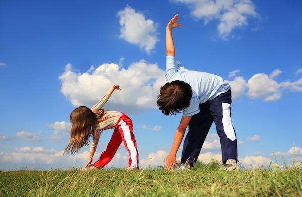 Egy kisfiú és egy kislány törzshajlítást végez egy nyári réten.