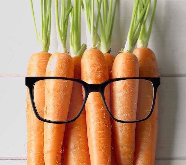 Egy csokor sárgarépán van egy fekete szemüveg, utalva ezzel a karotinoidok fontosságára szemünk egészségének megóvása érdekében.