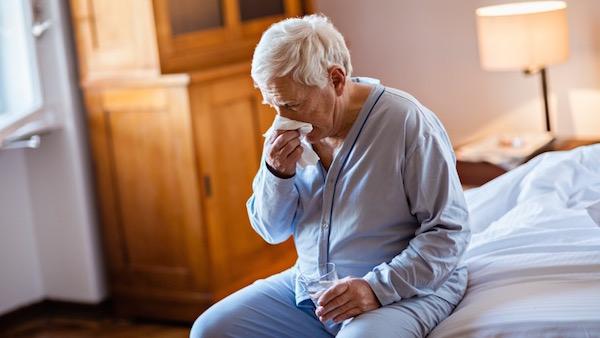 Idős férfi pizsamában ül az ágya szélén, fújja az orrát, kezében egy pohár víz.