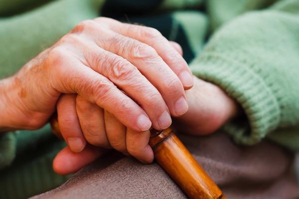 Idős ember keze nyugszik a botján.