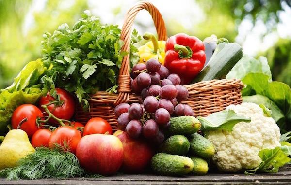 Egy nagy fonott kosár tele friss zöldséggel, gyümölccsel, fűszernövénnyel.