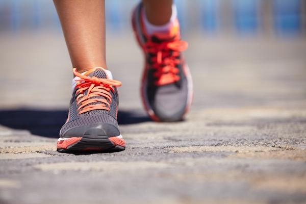 Gyalogló nő lábát látjuk edzőcipőben.