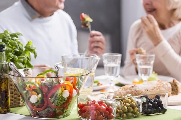 Idős házaspár asztalán csupa egészséges étel: friss saláták, zöldségek, olívabogyó, teljes kiőrlésű kenyér, olívaolaj és friss bazsalikom.