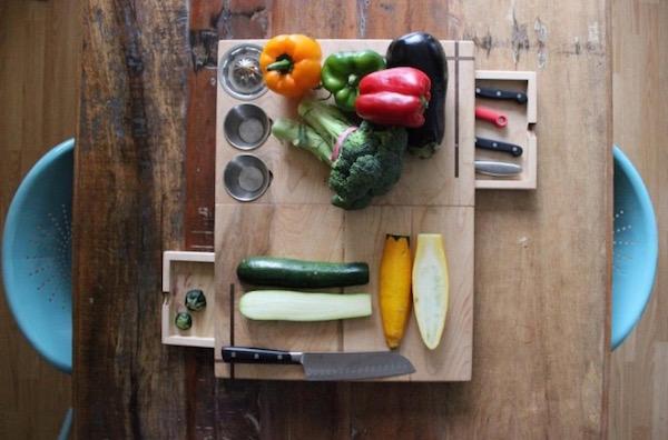 Felülről fotózott zöldségfélék egy vágódeszkán, amely egy fából készült asztalon áll, betolva két műanyag szék.
