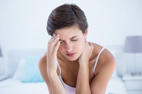 Középkorú nő az ágyán ülve migréntől szenved.