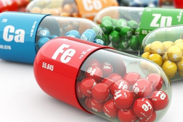 Ásványi anyagok kis színes kapszulákba helyezve: kalcium, vas, cink, foszfor.