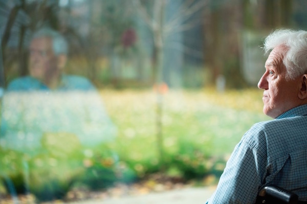 Egy óriási ablak előtt ül egy idős férfi a székében, szomorúan réved a semmibe a tekintete.