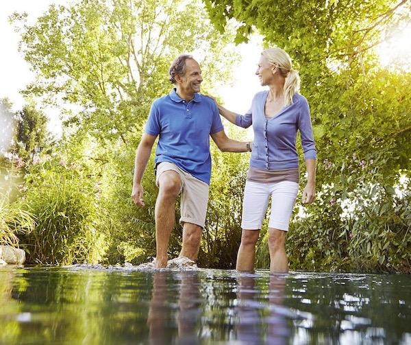 Víztaposást végez egy 50 év körüli házaspár egy hideg vízű patakban, amely lábszárközépig ér.