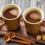 Két pohárban forró kakaó, mellettük kanál és nádcukor.