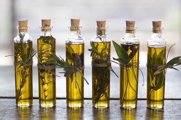 Házi készítésű fűszerolajak hosszúkás üvegekben, mindegyik átkötve zsinórral, mellétűzve egy szál friss fűszerággal.