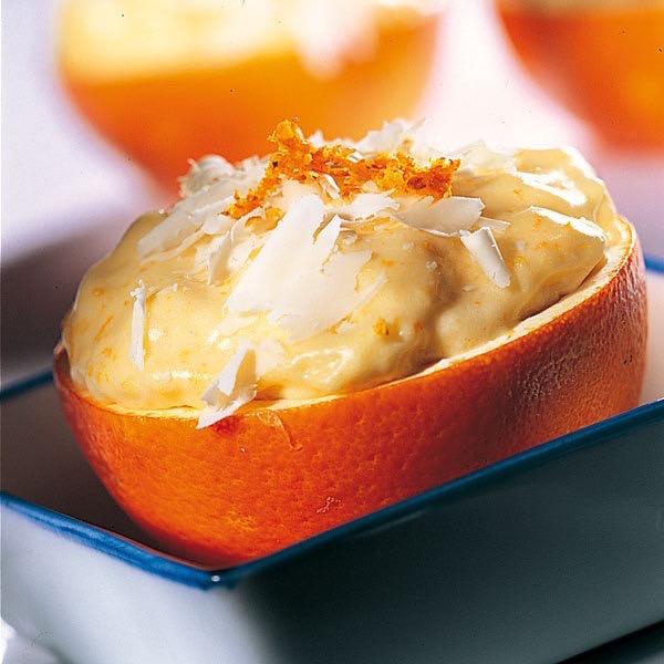Narancskrém egy félbevágott narancs belsejében tálalva.
