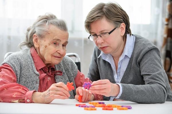 Idős, demens nénivel egyszerű puzzle-t játszik a lánya.