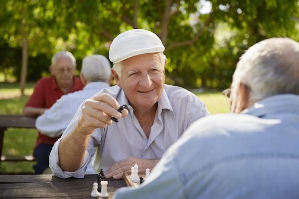 Egy parkban idős emberek sakkoznak a kinti asztaloknál a jó időben.