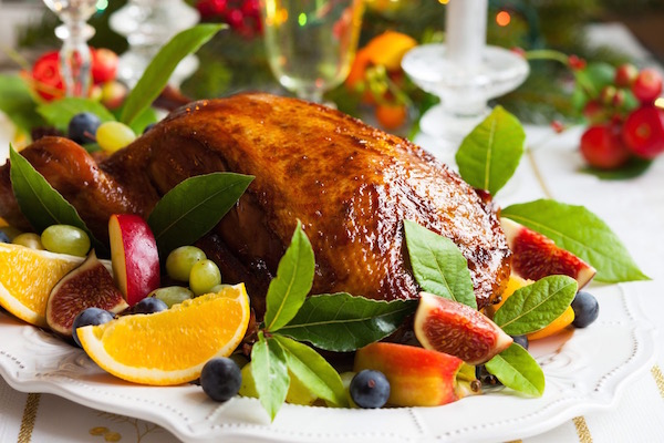 Frissen kisült pecsenyekacsa gyümölcsökkel tálalva a karácsonyi asztalon.
